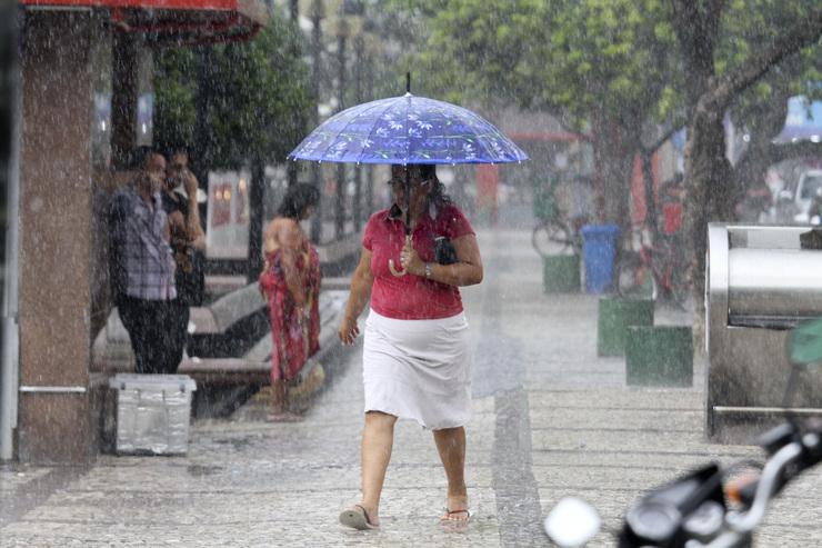 Mulher com guarda-chuva caminha sob chuva pela Praça do Ferreira