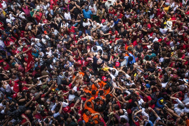 Lula sendo carregado nos ombros e cercado por uma multidão que tenta com o braços esticados tocá-lo