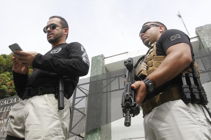 Secretário André Costa com telefone na mão ao lado de policial armado