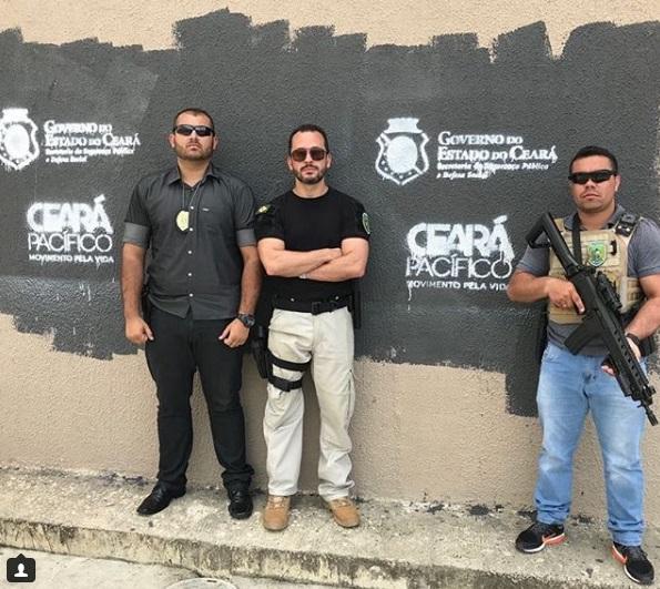 André Costa ao lado de dois agentes de segurança, com muro pintado de preto e com marcas do Governo do Estado e do Ceará Pacífico
