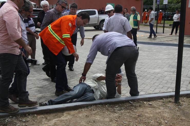 Segurança baleado caído enquanto Camilo e pessoas próximas observam e tentam ajudar