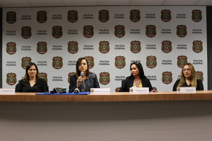 Quatro delegadas sentadas à mesa e apresentando resultados