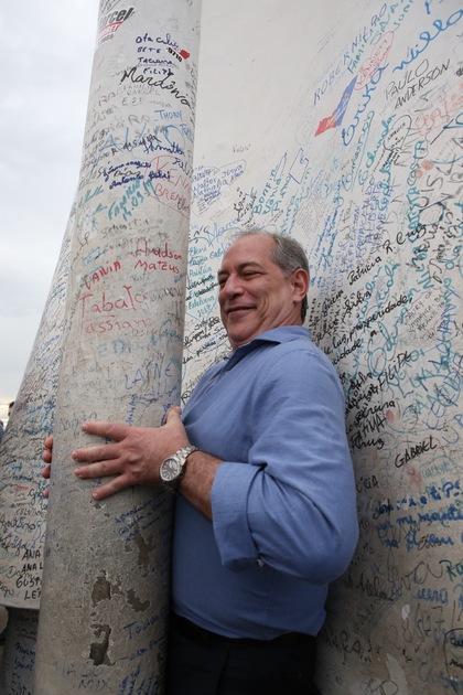 Ciro se espreme para passar por poste repleto de inscrições de devotos