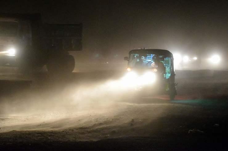 Carros circulam em meio a densa camada de poeira no ar