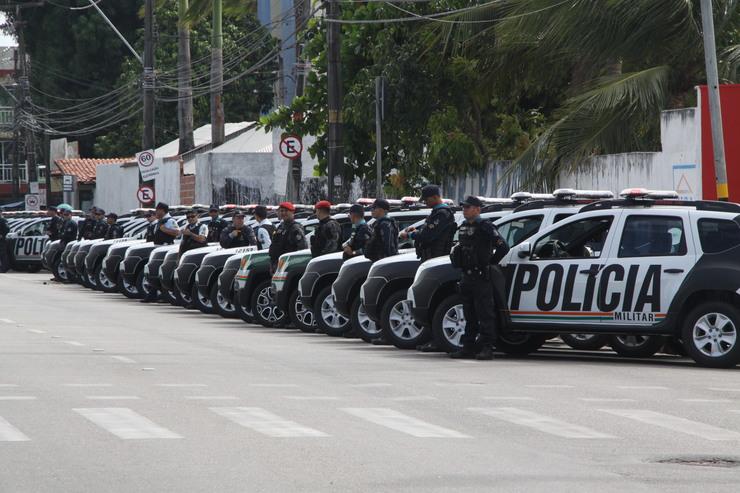 Policiais militares em frente às viaturas da PM