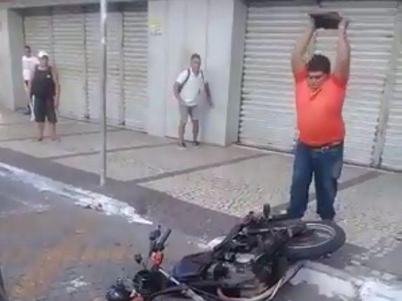 Homem tenta destruir moto com pedra