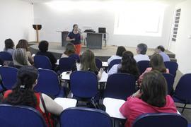 A foto mostra pessoas que participam do seminário sobre aleitamento materno e uma palestrante