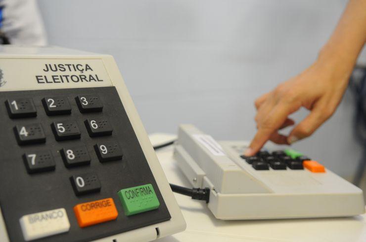 Mão de eleitor usando urna eletrônica (Foto: )