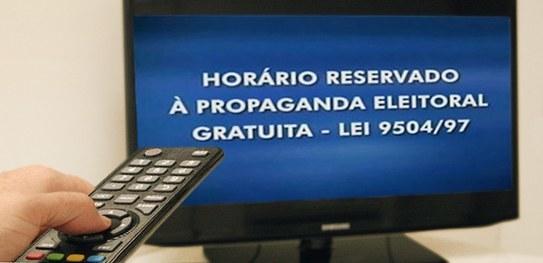 Controle remoto apontado para a TV, exibindo horário eleitoral (Foto: )