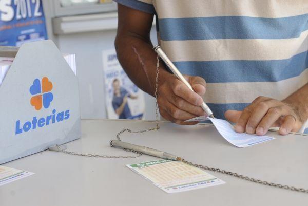Homem marcando os números na cartela da loteria da Quina