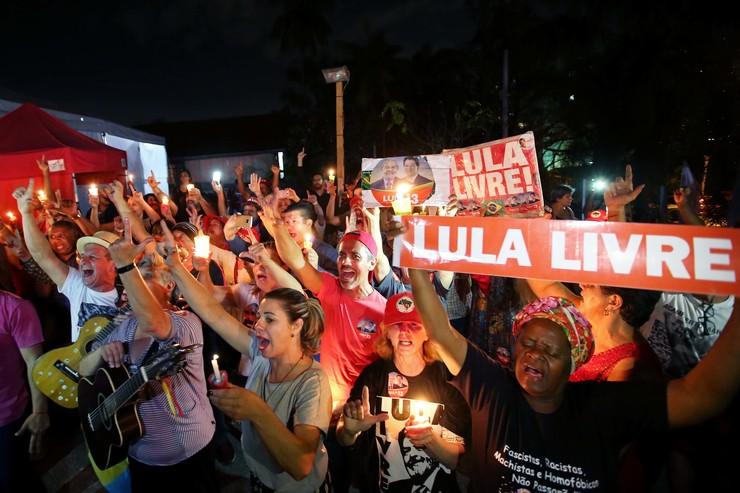 Apoiadores em vigília noturna, com faixas, cartazes e velas