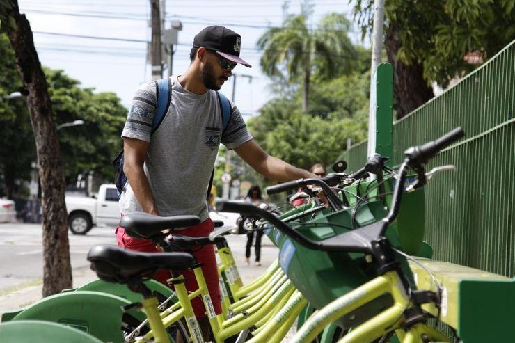 Homem retirando bicicleta da estação de bicicleta compartilhada