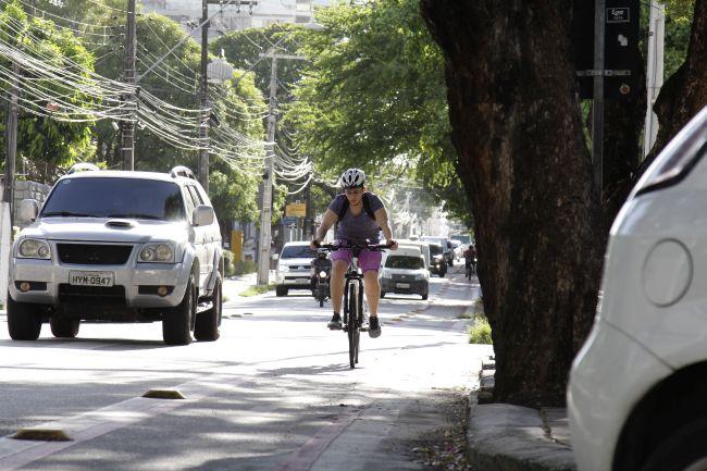 Mulher se deslocando de bicicleta pela ciclovia em rua de Fortaleza