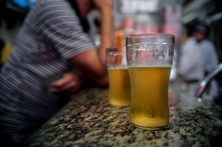 Copos de cerveja em uma balcão e uma pessoa ao fundo