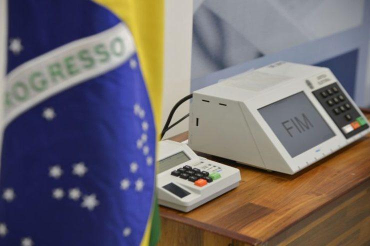 Foto mostra bandeira do Brasil ao lado de urna