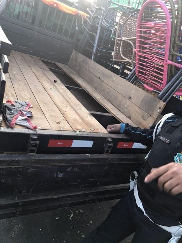 A foto mostra a carroceria de um caminhão com uma tábua levantada e o fundo falso