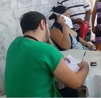 Médico atendendo pacientes na calçada do hospital em mesa e cadeira de plástico
