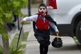 Menino corre fantasiado de vampiro para o Halloween