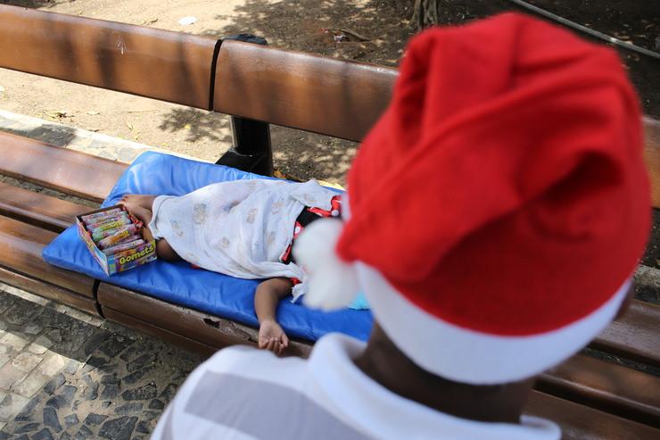 Um morador de rua usa gorro de papai noel. No fundo, uma criança dorme deitada no banco da praça
