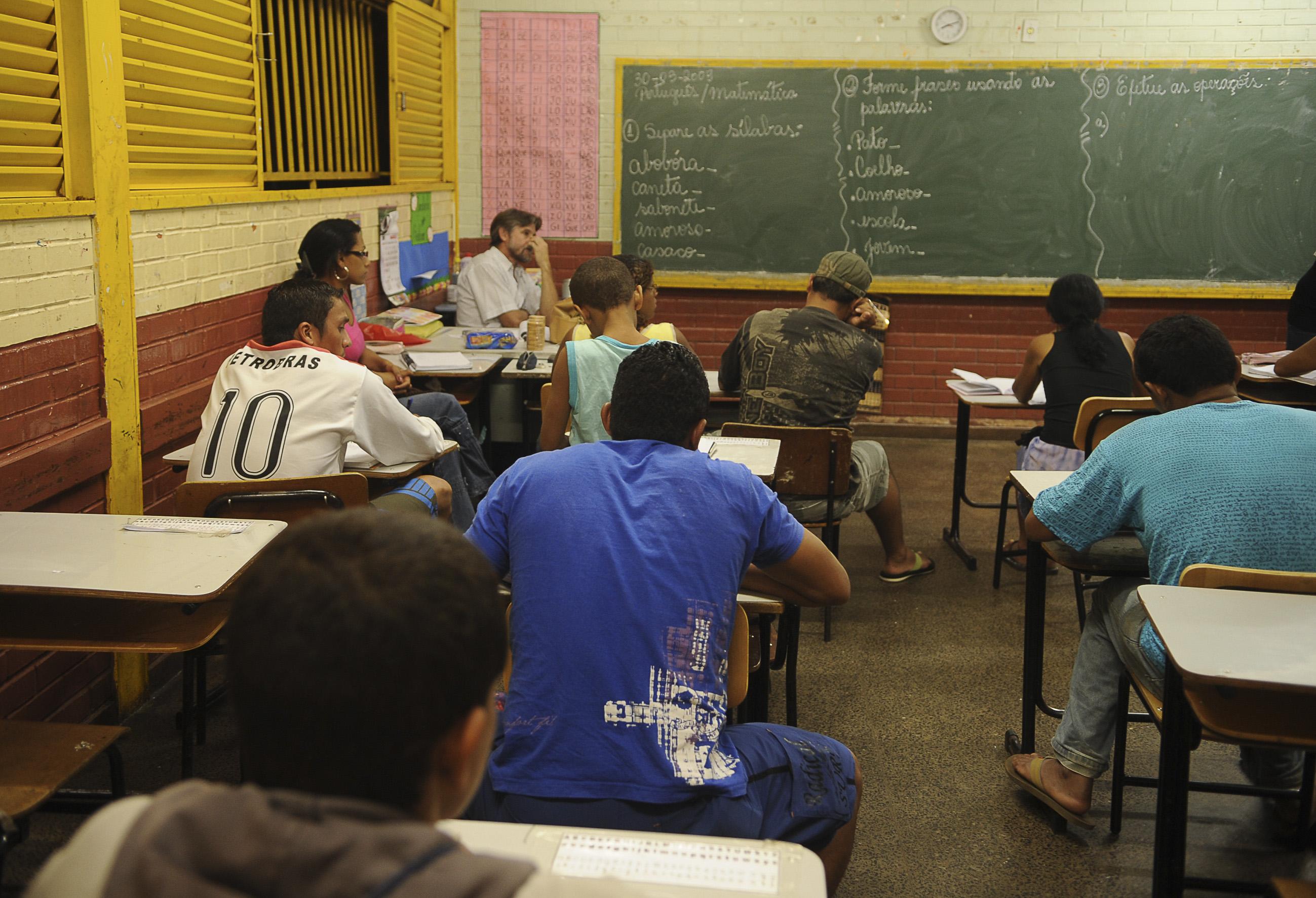 Alunos de frente para um quadro negro assistem aula (Foto: )