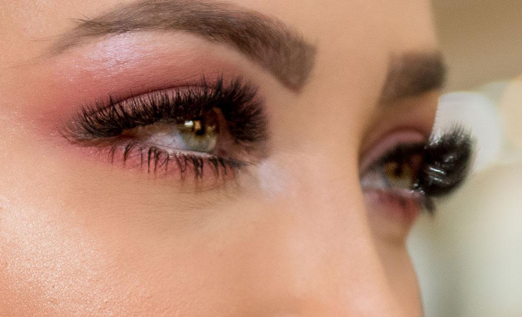 Olhos de uma mulher, com cílios alongados e sombra rosada