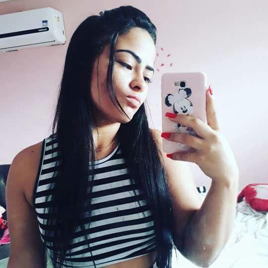 Victoria Régia Pedrosa seguraça celular em frente a espelho (Foto: )