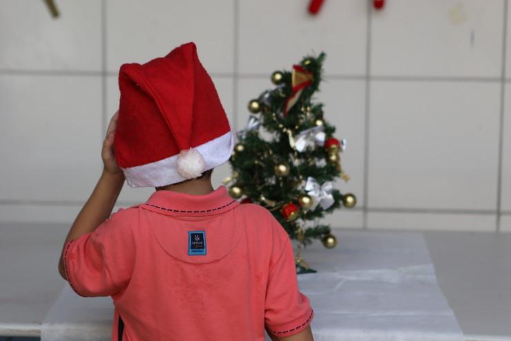 Criança frente a árvore de Natal