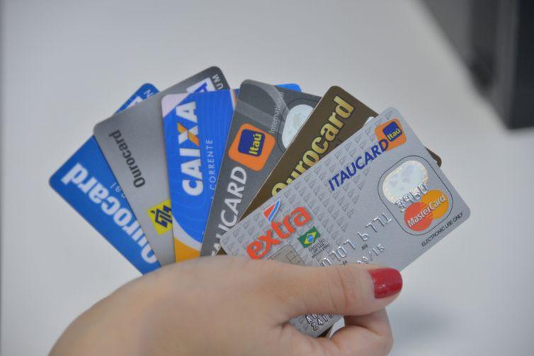 Uma pessoa segurando vários cartões de crédito de bandeiras diferentes