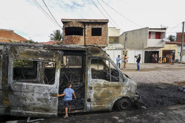 Criança próxima a transporte escolar incendiado