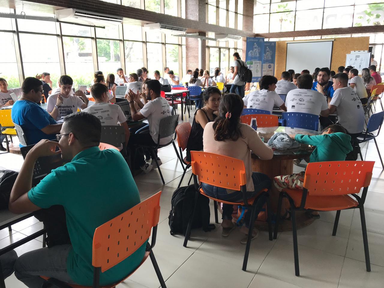 Sala de aula com uma pessoa apresentando-se e os alunos, que aparecem de costas para a foto, assistindo