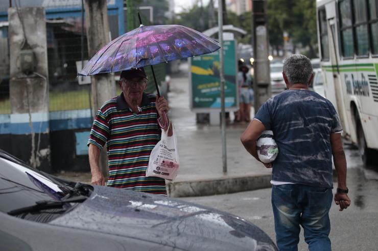 A foto mostra duas pessoas atravessando a rua em um dia de chuva. Uma delas carrega um guarda-chuva rosa e a outra não possui o equipamento