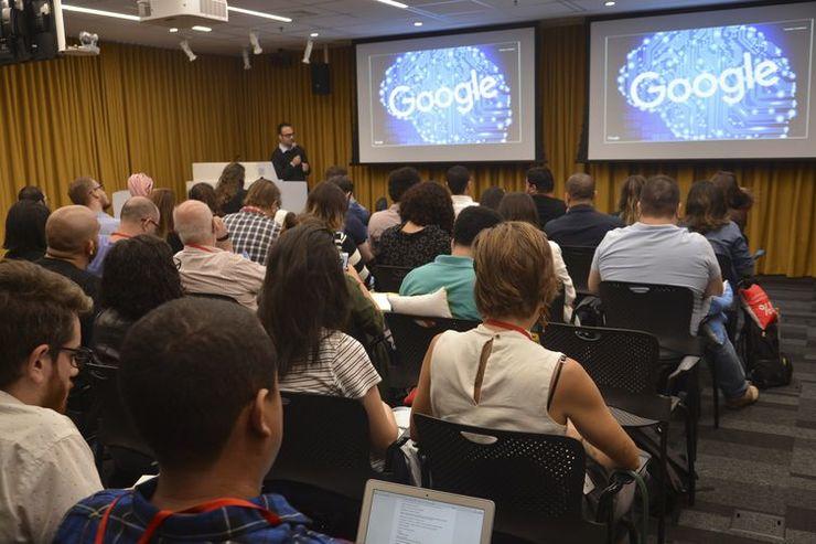 A foto exibe um auditório com várias pessoas, incluindo palestrante e plateia. Existem telões ao fundo com o logo do Google.