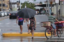 a chuva mostra duas pessoas atravessando a rua, uma de guarda-chuva e outra sem. Também há um ciclista no lado direito da foto