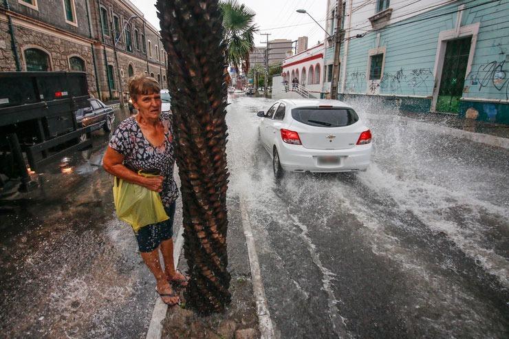 Idosa tenta desviar de água no meio de fio de via