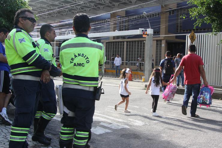 No lado esquerdo da imagem, existem três agentes da AMC olhando para a via, enquanto um pai atravessa a rua com duas crianças em uma faixa de pedestre.