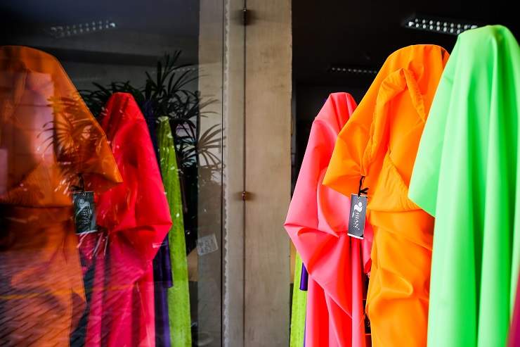 Tecidos amarelo, rosa, laranja e verde em tons neon expostos em uma vitrine e refletidos no vidro