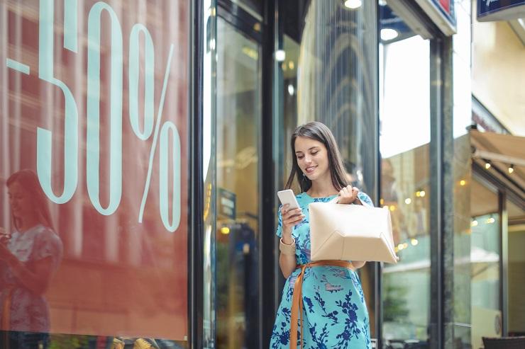 Mulher loira faz compras em frente a um cartas com 50% de promoção