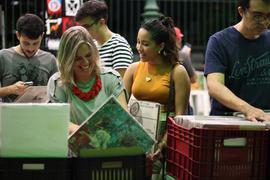 Grupo de pessoas comprando vinis no Mercado dos Pinhões. Na frente, duas mulheres olham para um disco e estão sorrindo.
